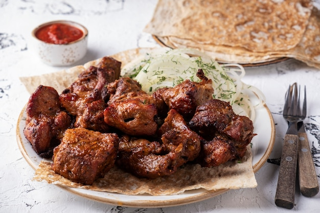 Grilled shish kebab on a plate serbed  fork and knife