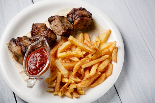 Grilled shish kebab served with french fries and sauce on white wooden table