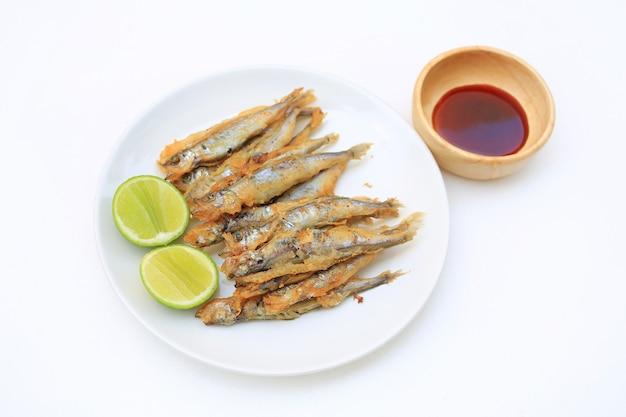 シシャモのグリル魚のグリルにレモンとスイートソースを添えて皿に盛り付けます