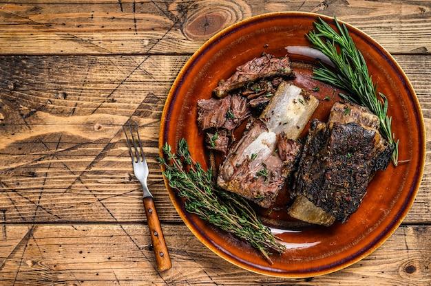 소박한 접시에 백리향을 곁들인 구운 짧은 쇠고기 갈비. 나무 배경입니다. 평면도. 공간을 복사합니다.
