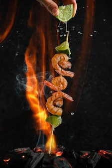 Grilled shrimp and mussel skewers over coal heat on fire and smoke background