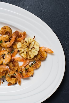 Grilled shrimp portion on a white plate with pineapple.