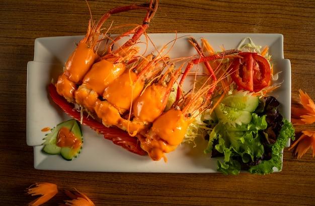 Жареные креветки с сыром в белой тарелке.