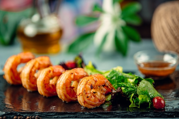Grilled shrimp with fresh herbs salad on black stone board