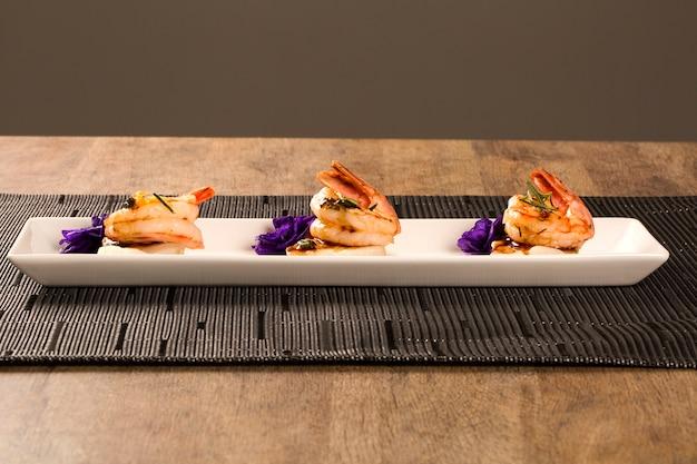 テーブルの白いプレートに生のネイルフィッシュを添えたエビのグリル