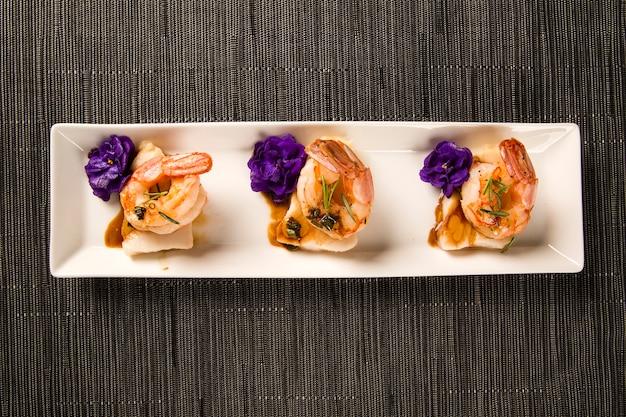 Жареные креветки с сырой гвоздями на белой тарелке за столом