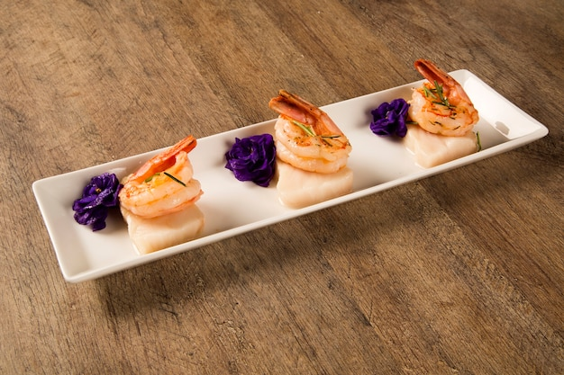 Grilled shrimp with raw nail fish on white plate at table