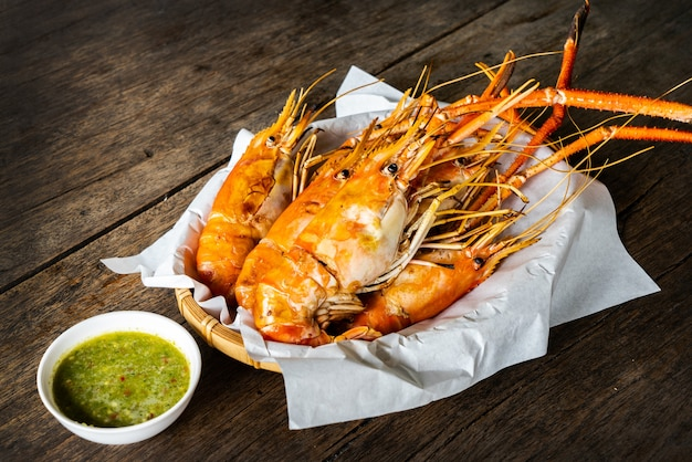 Grilled shrimp with sauce on wooden table.  seafood concept