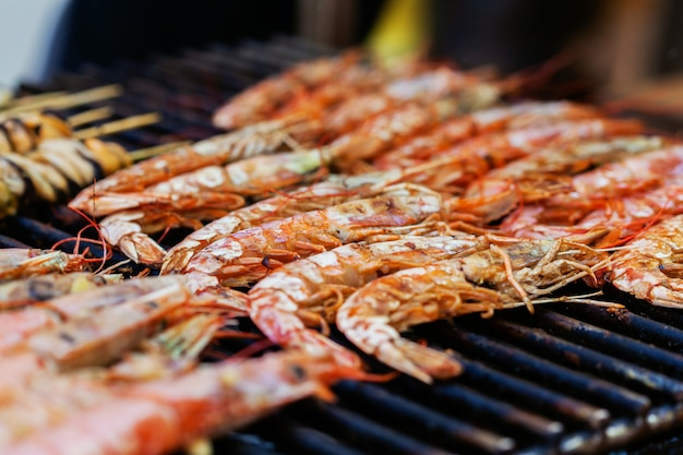 Grilled shrimps or barbecued shrimp cooking on charcoal stove. street food festival
