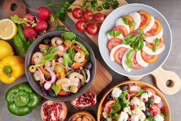 Grilled shrimps and fresh vegetable salad. healthy food. flat lay. italian caprese salad with tomatoes, basil, mozzarella, italian traditional caprese salad ingredients. mediterranean, greek salad.