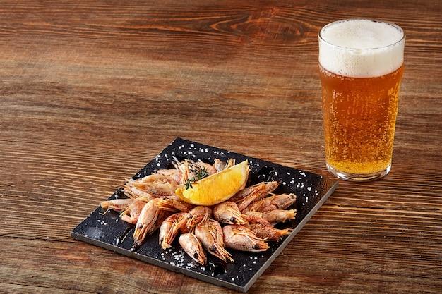黒板鍋にエビのグリル、木製テーブルにビール