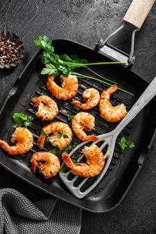 Grilled shrimps on pan on dark