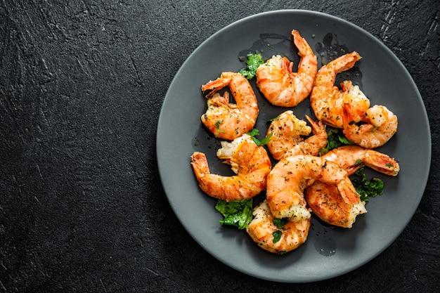 Grilled shrimps on plate on dark