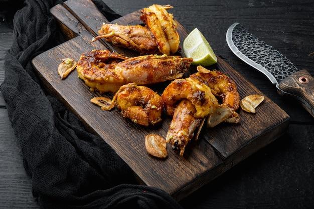 Grilled shrimps or prawns served with mango chutney crispy garlic set, on wooden board, on black wooden table