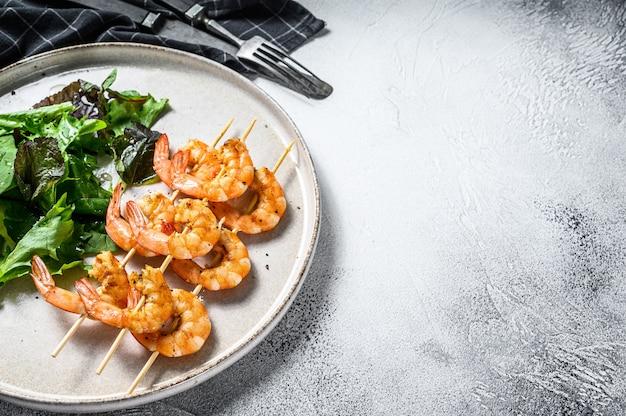 Grilled  shrimps, prawns skewers with herbs, garlic, brochette kebab. .