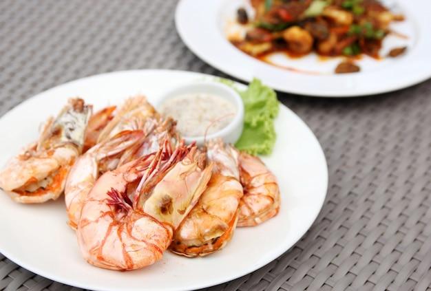 Gamberi alla griglia con salsa di frutti di mare sulla piastra bianca