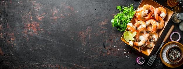 어두운 시골 풍 테이블에 향신료, 허브, 양파 링으로 구운 새우
