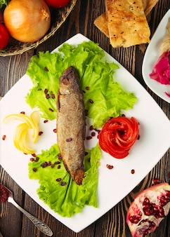 Grilled silver fish served with lemon, lettuce, tomato and pomegranate seeds.