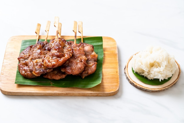 Grilled skewered milk pork with white sticky rice