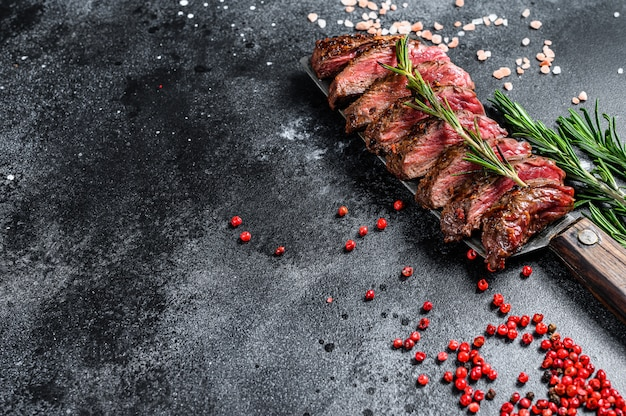 Grilled skirt, machete steak. marble meat beef. black surface. top view. copy space
