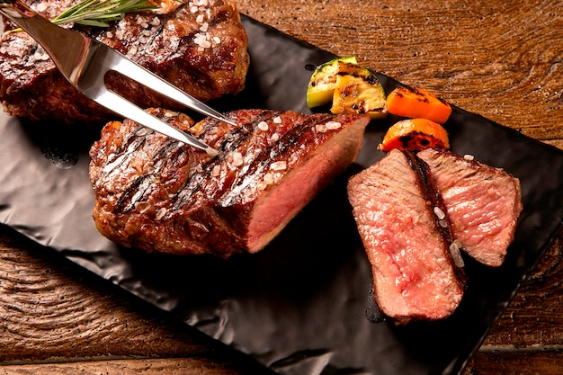 Grilled sliced beef steak on a black cutting board on the wooden table.