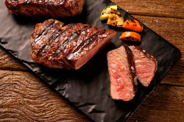 Нарезанный на гриле стейк из говядины на черной разделочной доске на деревянном столе.