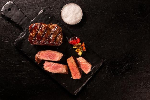 블랙 테이블 위에 블랙 커팅 보드에 구운 된 슬라이스 쇠고기 스테이크.