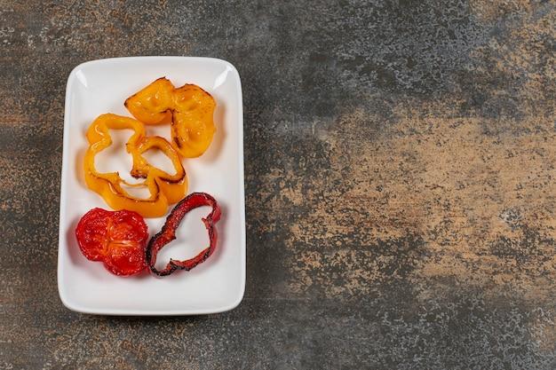 Жареный нарезанный болгарский перец на белой тарелке.