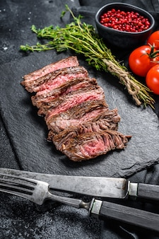 Grilled sliced flank steak with seasonings and spices. black background. top view.