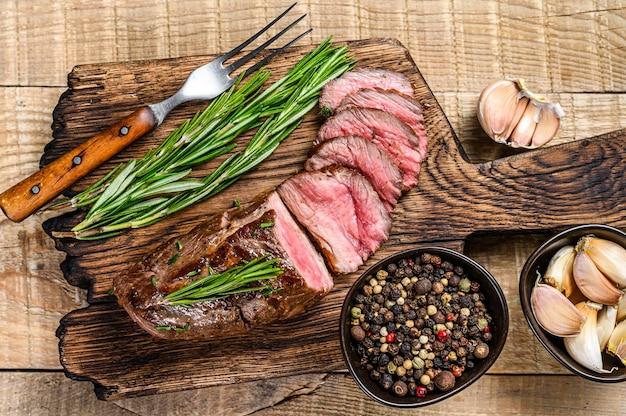 커팅 보드에 구운 얇게 썬 양고기 등심 고기 스테이크. 나무 배경입니다. 평면도.