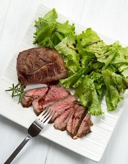 Grilled sliced meat fillet on dish and salad