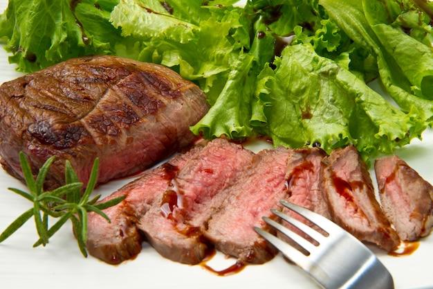접시와 샐러드에 구운 된 고기 필렛 구이