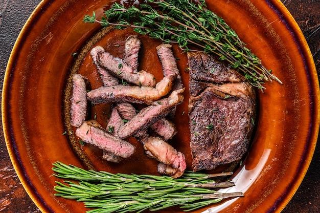 Grilled sliced rib eye or ribeye beef meat steak on a rustic plate.