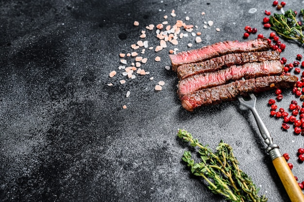Grilled sliced rib eye steak with spices. bbq beef. black background. top view. copy space.