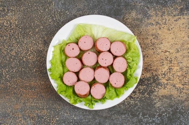 Salsicce e lattuga affettate alla griglia sul piatto bianco.