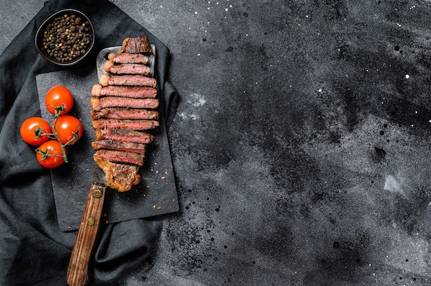 Grilled sliced sirloin steak on a meat cleaver. black background. top view. copy space