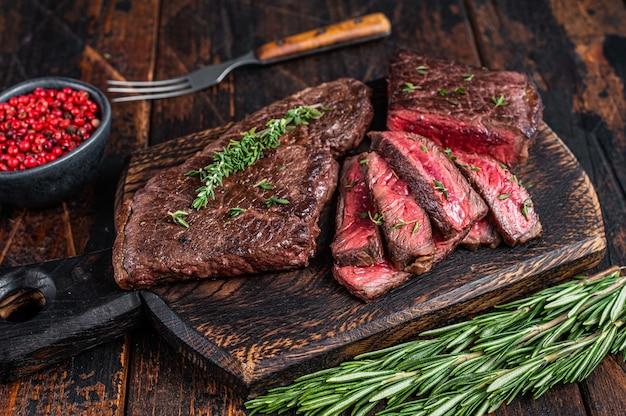 Нарезанный на гриле стейк из говядины на разделочной доске с зеленью. темный деревянный фон. вид сверху.