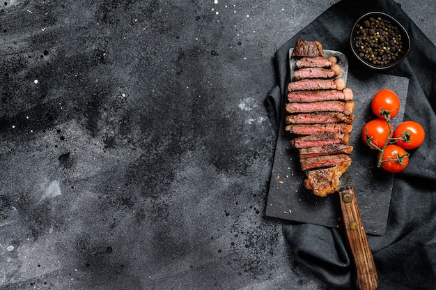 Grilled sliced strip loin steak on a meat cleaver.  .