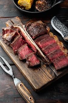 Нарезанный на гриле стейк на косточке, на деревянной сервировочной доске, на фоне старого темного деревянного стола