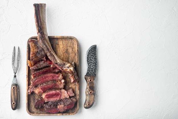 구운 슬라이스 토마 호크 쇠고기 스테이크 세트, 나무 서빙 보드, 흰 돌 테이블, 평면도 평면 누워