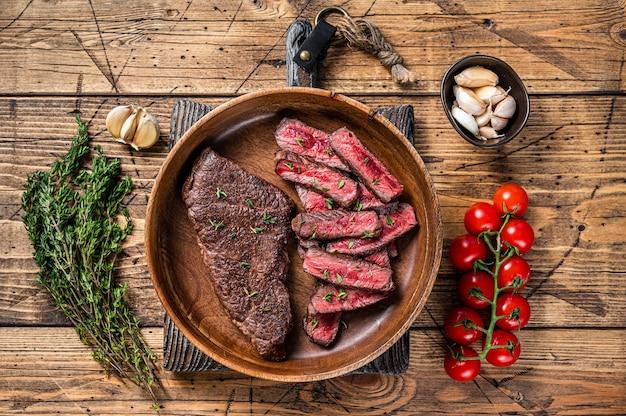 Жареные нарезанные ломтиками верхнее лезвие или стейк из говядины денвер на деревянной тарелке с зеленью. деревянный фон. вид сверху.