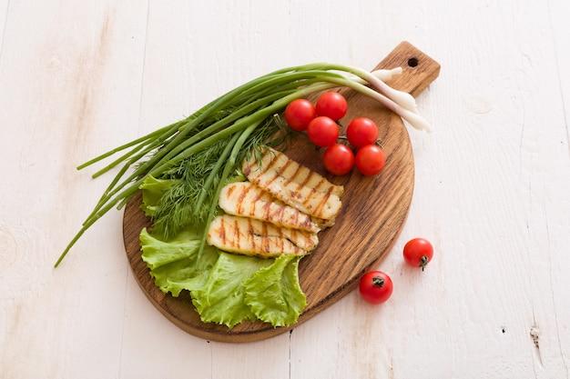 Ломтики домашнего сыра халуми на гриле с зеленым салатом, зеленью и органическими помидорами
