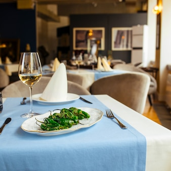 Grilled spanish green padron peppers on the restaurant table