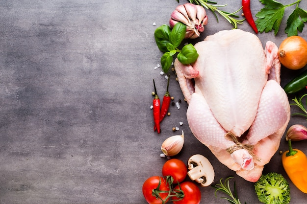 Жареный пряный цыпленок, овощи на сером фоне. вид сверху.