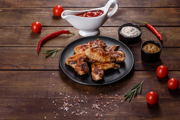 향신료와 허브를 곁들인 어두운 배경에 구운 매운 닭 날개