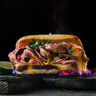暗い背景に木製のまな板に火の炎でグリルスパイシーステーキサンドイッチをクローズアップ
