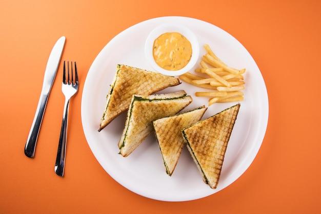 Жареные бутерброды со шпинатом или кукурузой с сыром на красочном фоне. выборочный фокус
