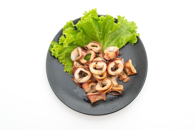 Grilled squid on black plate isolated on white background