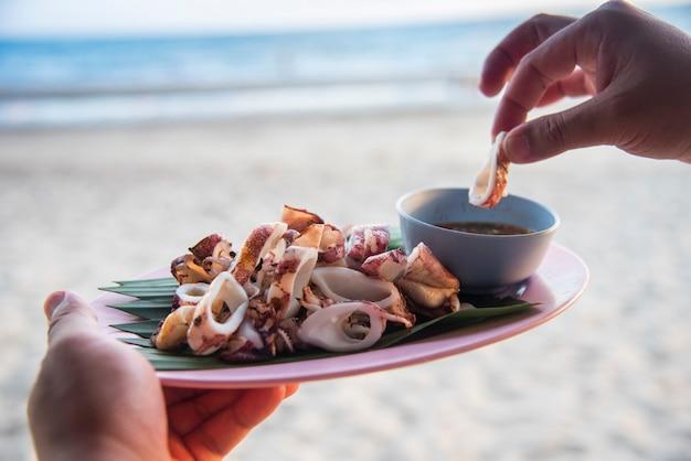 해변 바다 배경에 구운 오징어 / 태국 해산물 소스와 함께 접시에 오징어 슬라이스