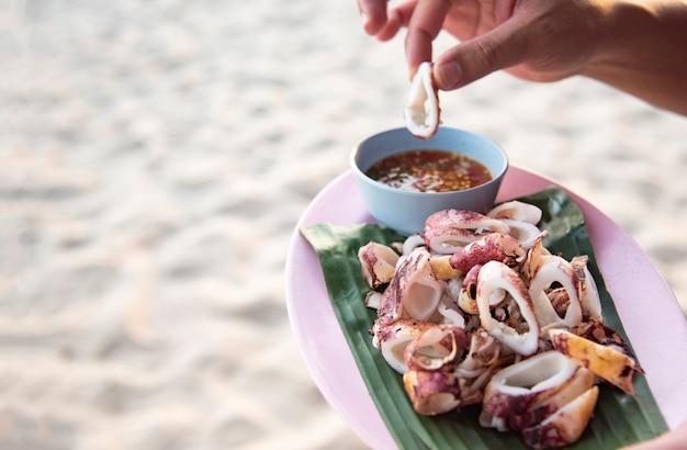 해변 바다에 구운 오징어-손에 태국 해산물 소스와 함께 접시에 오징어 슬라이스